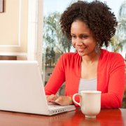 woman with orange shirt smiling on a computer